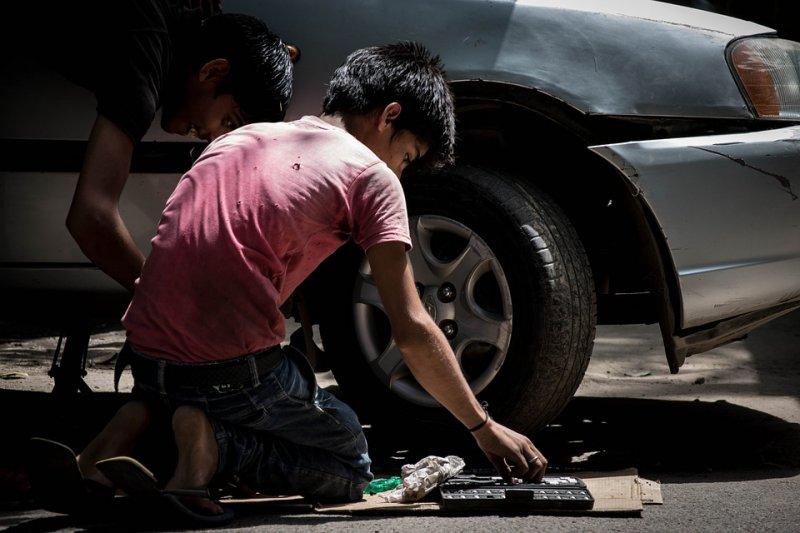 due minori che lavorano vicino una macchina